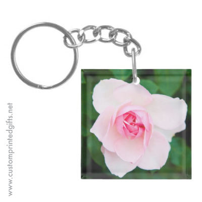 Square keychain with a romantic, pale pink rose and green leaves in the background
